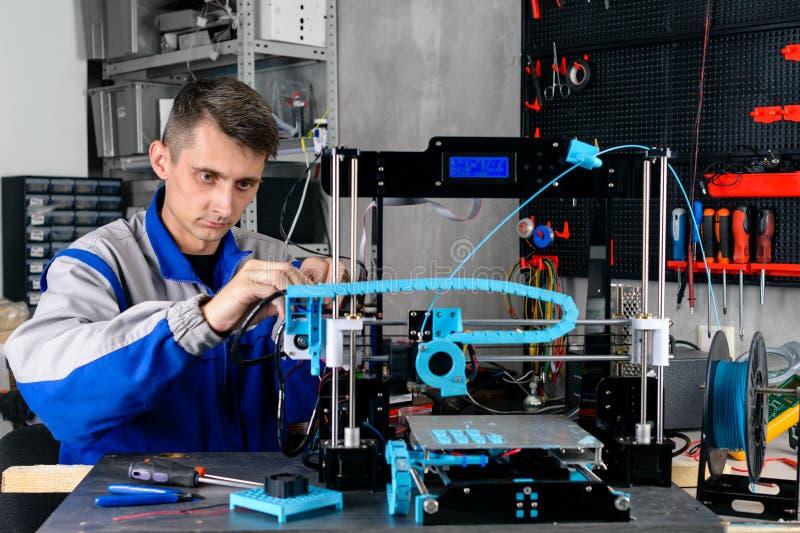 Junger Designeringenieur unter Verwendung eines Druckers 3D im Labor stockfotografie