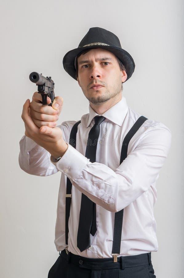 Junger Detektiv zielt mit Gewehr mit Schalldämpfer lizenzfreie stockbilder