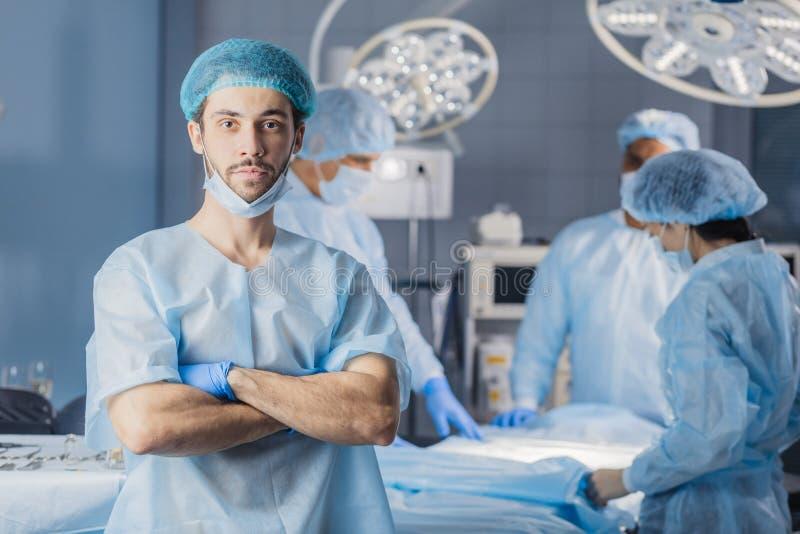 Junger Doktor, Chirurg, der medizinischen Schutzanzug im Operationsraum trägt lizenzfreie stockfotos