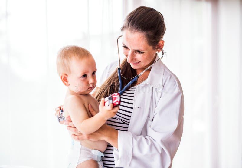 Junger Doktor, der ein Baby in einem Büro überprüft stockfotos