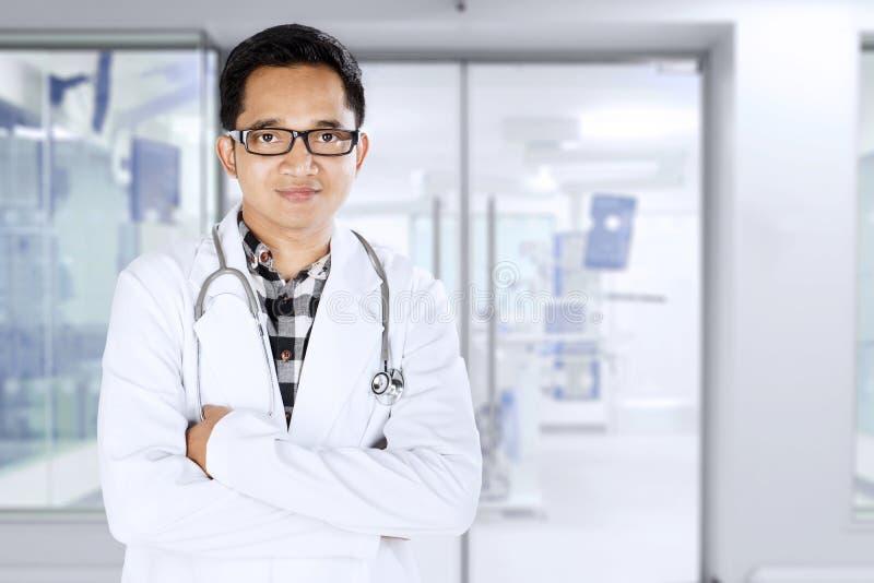 Junger Doktor, der im medizinischen Raum steht stockfotos