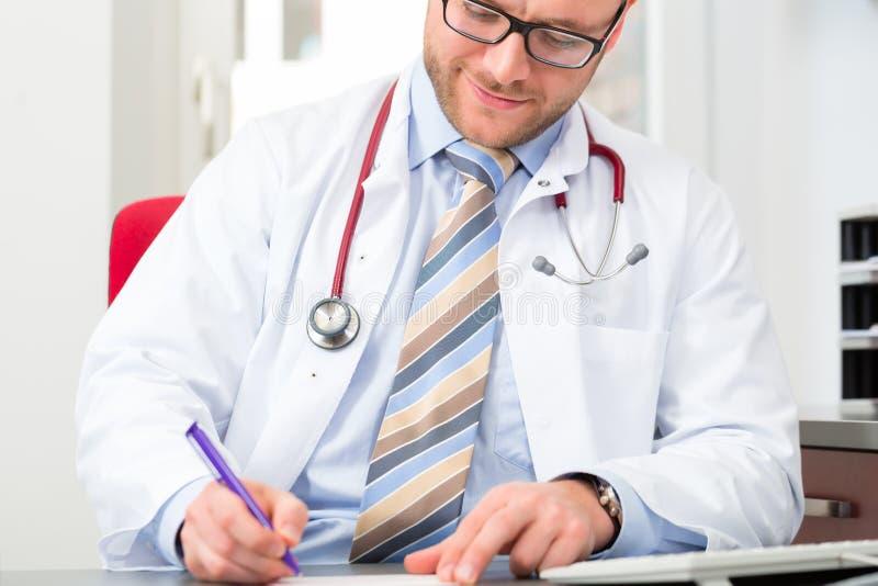 Junger Doktor, der medizinische Verordnung schreibt stockbilder