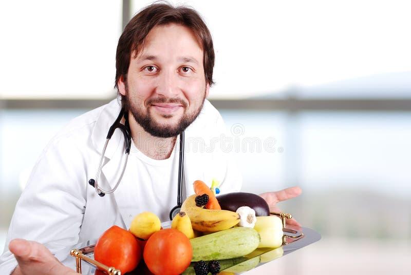 Junger Doktor im Krankenhaus mit viel der Früchte lizenzfreies stockbild