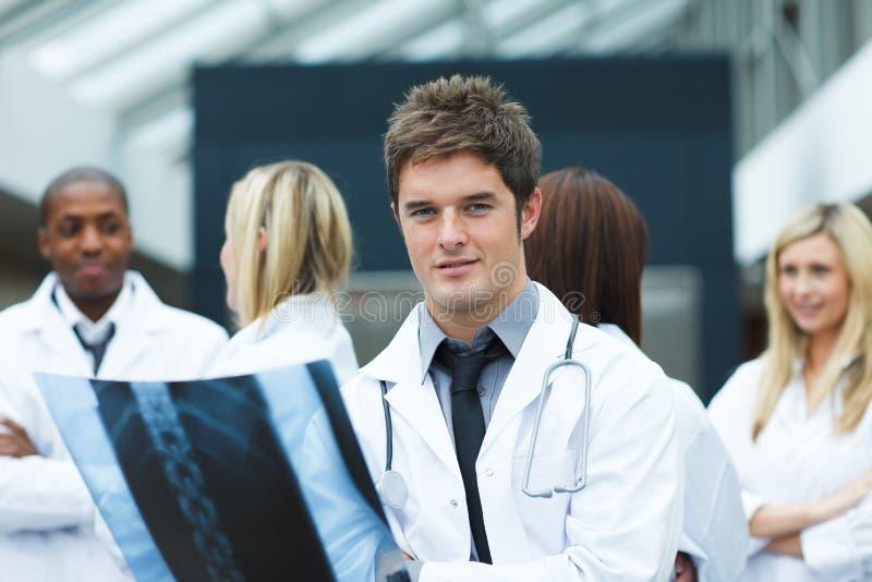 Junger Doktor mit einem Röntgenstrahl, der die Kamera betrachtet lizenzfreie stockfotos