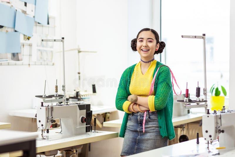 Junger dunkelhaariger asiatischer Designer in einer grünen Wolljacke glücklich lächelnd stockfotos