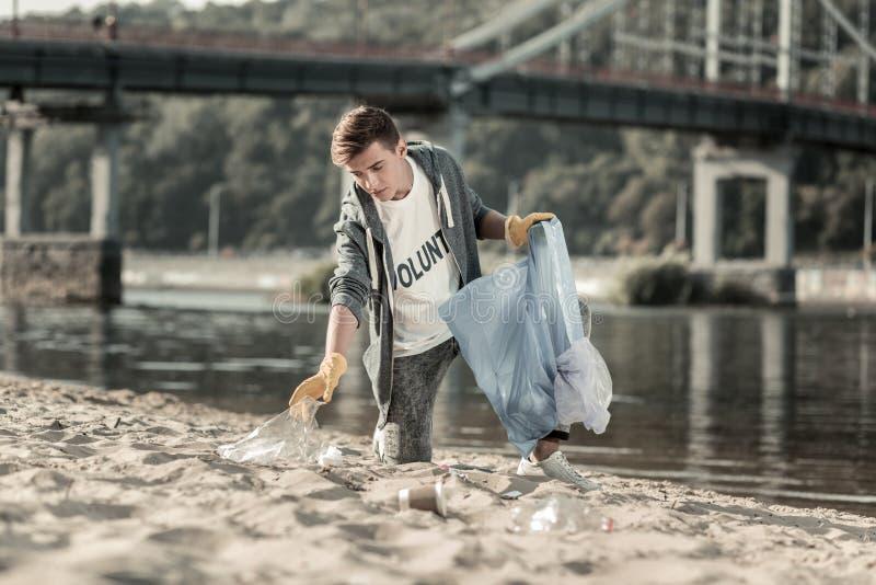 Junger dunkelhaariger Freiwilliger, der seinen Tag den Sand säubernd auf dem Strand verbringt lizenzfreie stockfotos