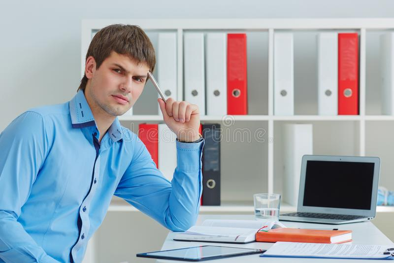 Junger durchdachter kaukasischer Geschäftsmann, der am Büroarbeitsplatz gerade schaut zur Kamera sitzt stockfotografie