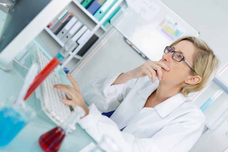 Junger durchdachter weiblicher Chemiker, der im Labor arbeitet stockbilder