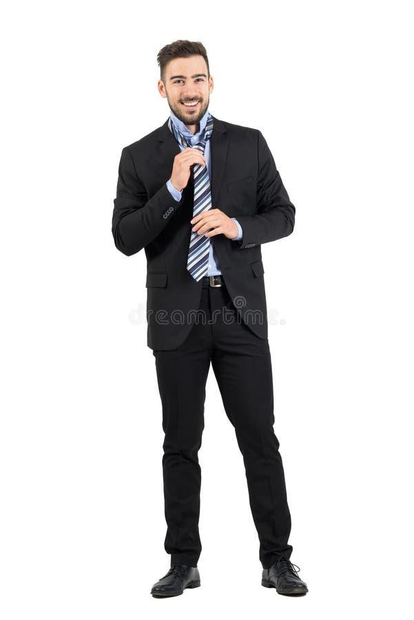 Junger eleganter Geschäftsmann in der Klage, die Krawatte bindet und justiert stockfoto