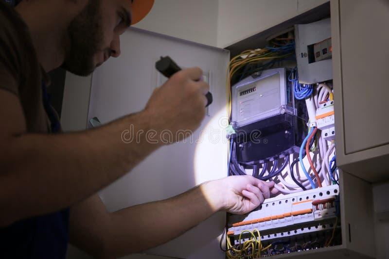 Junger Elektriker mit Taschenlampe nahe Schalterkasten lizenzfreie stockfotos