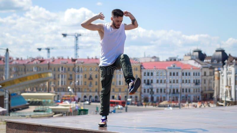 Junger emotionaler Mann mit den Tätowierungen, die auf den Stand mit seinem Bein herauf - Mitte der Stadt auf dem Hintergrund tan lizenzfreies stockbild