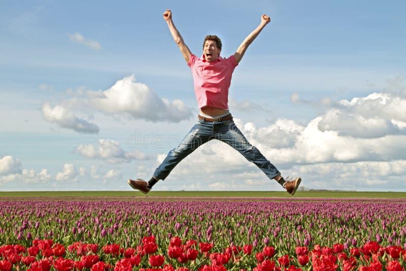Junger enthousiastic Kerl, der oben springt lizenzfreies stockfoto