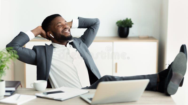 Junger entspannter Geschäftsmann genießen hörende Musik im Büro stockbild