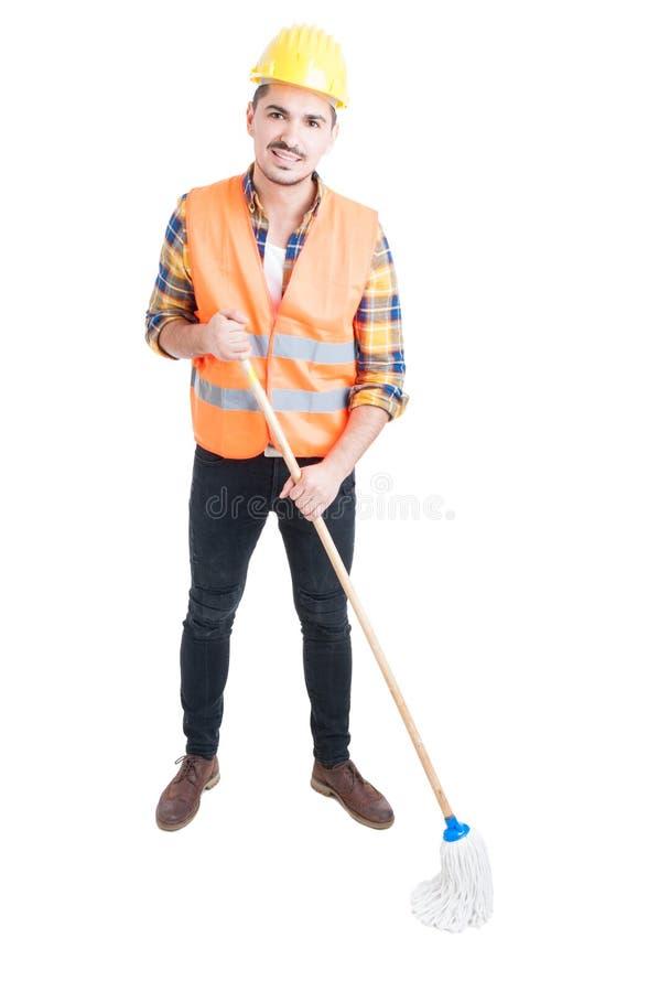 Junger Erbauer mit dem Mopp, der bereit ist, den Boden zu säubern lizenzfreie stockfotos