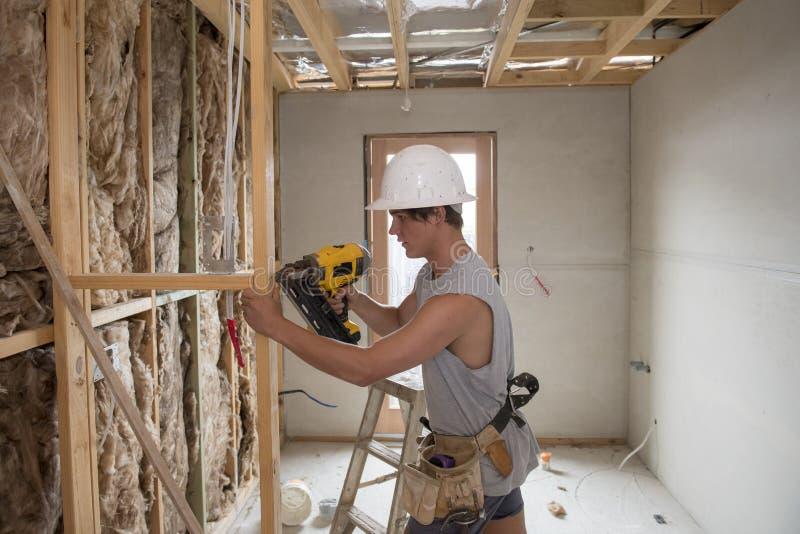 Junger Erbauerindustrieauszubildendmann auf seinem tragenden Schutzhelm 20s das Arbeiten mit Bohrgerät am industriellen Werkstatt lizenzfreie stockbilder