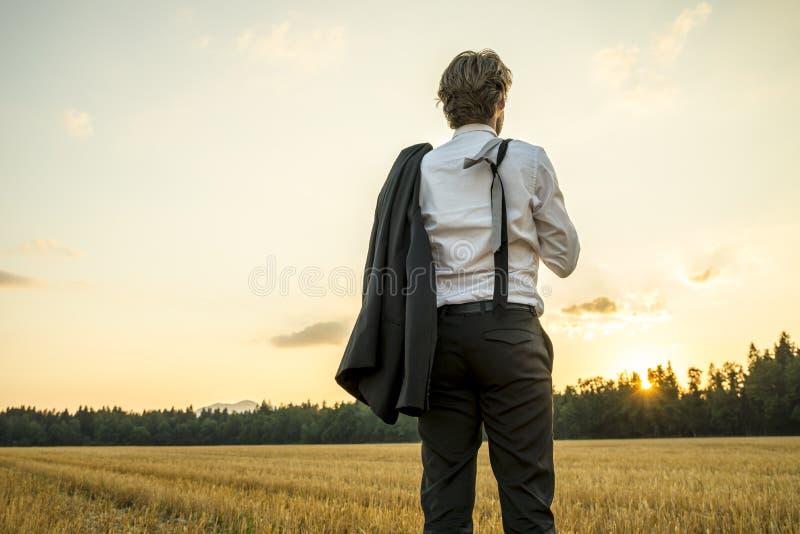 Junger erfolgreicher Geschäftsmann, der auf dem Weizengebiet schaut gaz steht stockbilder