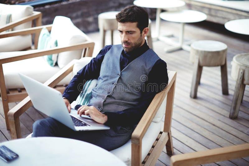 Junger erfolgreicher Geschäftsmann, der an einem Laptop beim Sitzen im Café während des Arbeitsbruchmittagessens arbeitet stockbilder