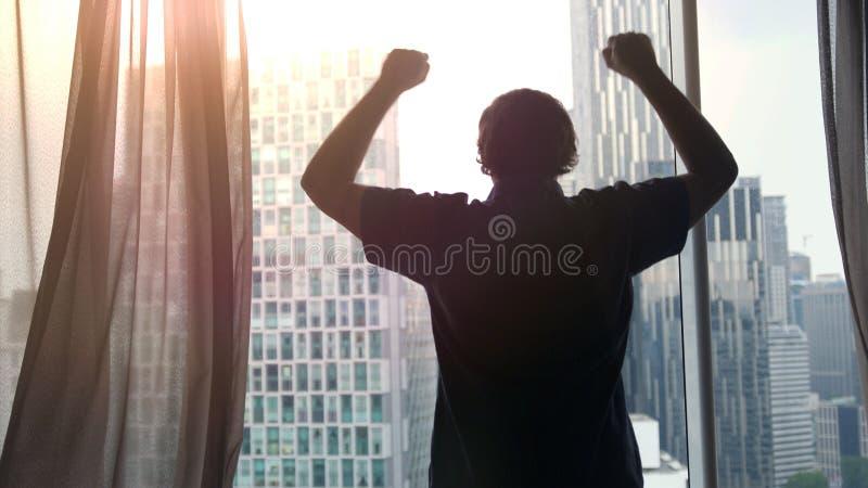 Junger erfolgreicher Reicher bewundern das Stadtzentrum mit Wolkenkratzern, die Ansicht Hände während des schönen Sonnenuntergang stockbild