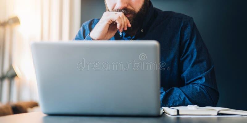 Junger ernster bärtiger Geschäftsmann, der bei Tisch vor dem Computer, Schirm betrachtend, Behälter sitzt und denken lizenzfreie stockfotografie