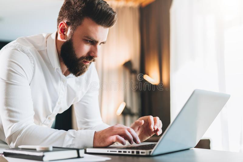 Junger ernster bärtiger Geschäftsmann, der im Büro nahe Tabelle steht und Laptop verwendet Mann arbeitet an Computer, überprüft E stockfotos