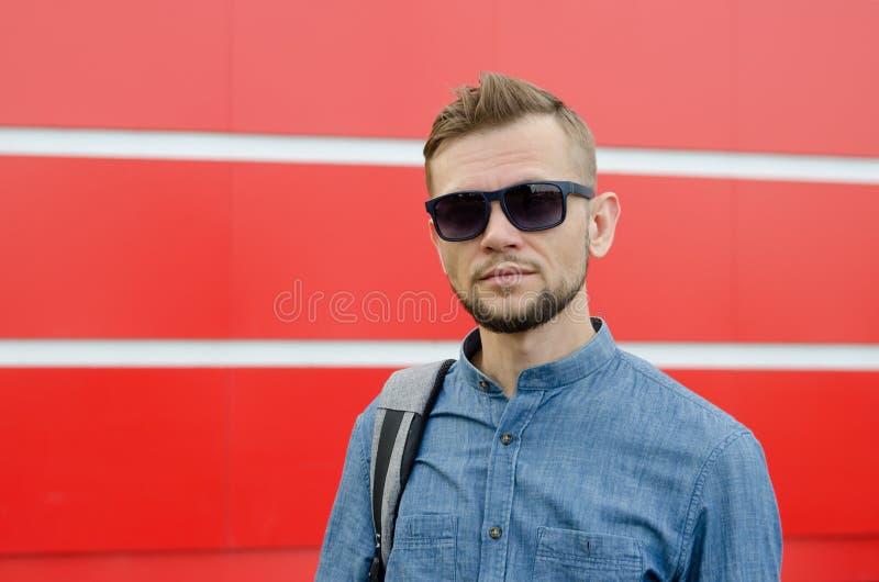 Junger ernster bärtiger Mann in der Sonnenbrille und im Denimhemd vor dem hintergrund der roten Wand stockfotos