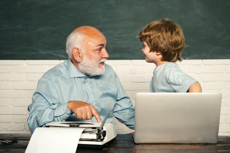 Junger ernster männlicher Schüler, der in der Schule studiert Ein Großvater und ein Kleinkind arbeiten mit Notizbuch Schüler, der lizenzfreie stockfotografie