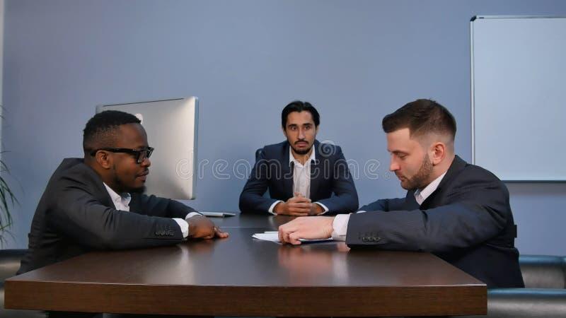 Junger ernster Mann, der die Papiere, sie, während der Sitzung im Büro aufmerksam lesend hält stockfoto