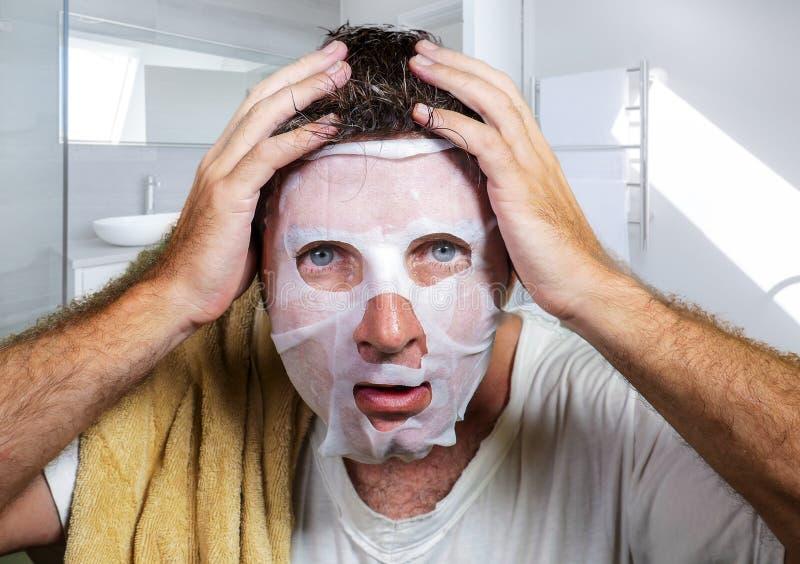 Junger erschrockener und ?berraschter Mann zu Hause unter Verwendung der Sch?nheitspapier-Gesichtsmaske, die die alternde Gesicht stockbilder