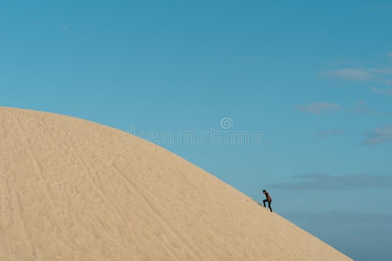 Junger erwachsener asiatischer Mann, der eine Sanddüne gegen Hintergrund des blauen Himmels klettert stockfotos