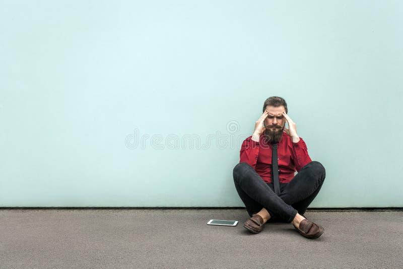 Junger erwachsener bärtiger Geschäftsmann sitzt aus den Grund lizenzfreie stockfotos