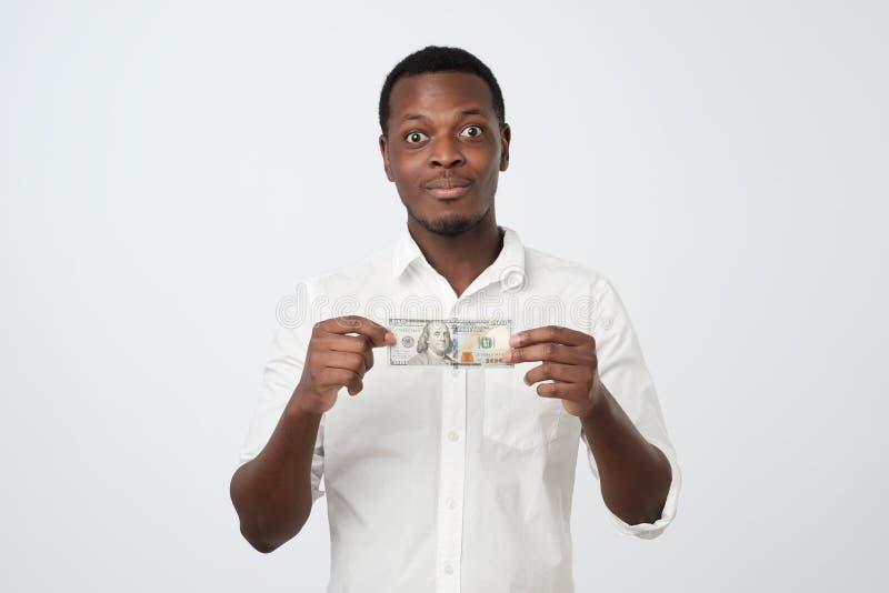 Junger erwachsener Geschäftsmann des frohen hübschen Afrikaners, der Dollar hält stockfotografie