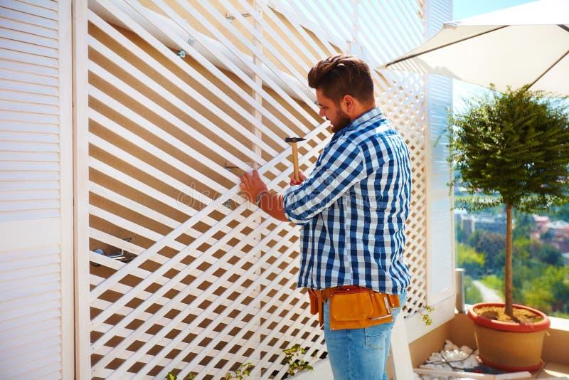 Junger erwachsener Mann, der die Hausmauer, durch das Gründen des hölzernen Gitters für Kletterpflanzen verziert stockfotografie
