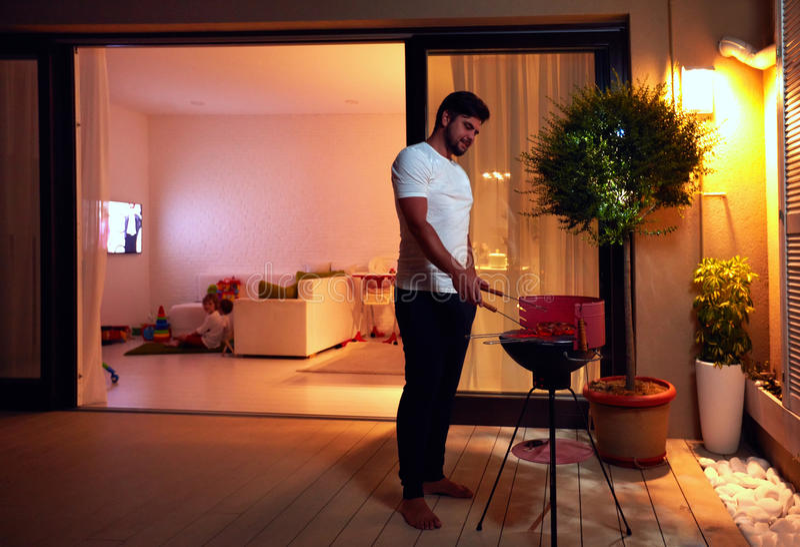 Junger erwachsener Mann, der Lebensmittel für Familie auf Abendpatio an ho zubereitet lizenzfreies stockfoto
