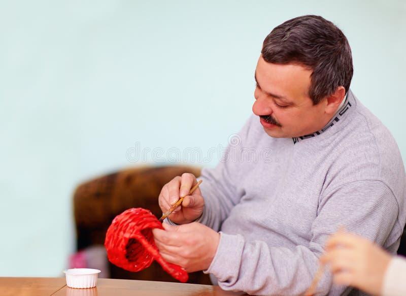 Junger erwachsener Mann engagierte sich in der Handwerksarbeit in Rehabilitationszentrum stockbild