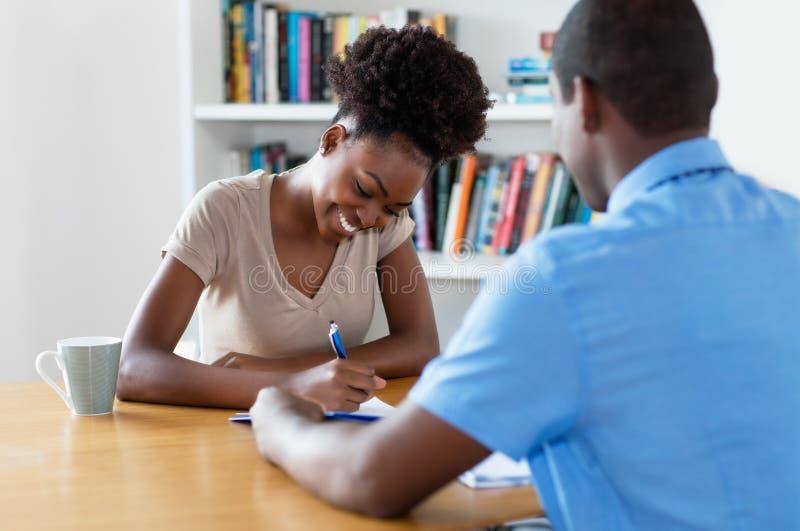 Junger erwachsener unterzeichnender Vertrag des Afroamerikaners nach Vorstellungsgespräch stockbilder