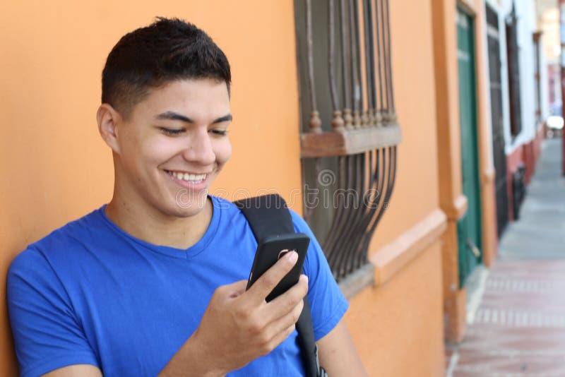 Junger ethnischer Mann unter Verwendung eines Mobiltelefons lizenzfreie stockfotografie