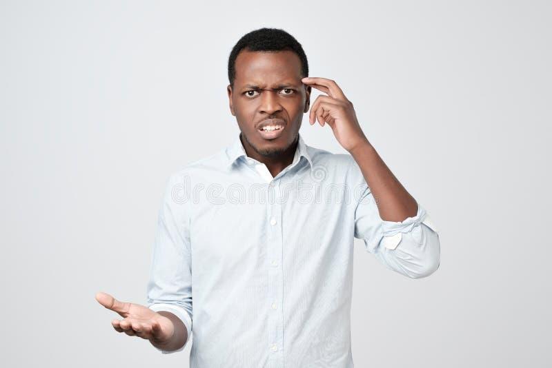Junger europäischer Mann im weißen unzufrieden gemachten Hemd runzelt die Stirn und schaut sullenly lizenzfreie stockfotografie