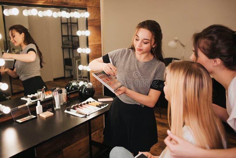 Junger Fachmann bilden Künstler mit Kunden im Raum Frau auf linker Grifflidschattenpalette und -bürste Blondine und lizenzfreie stockfotografie