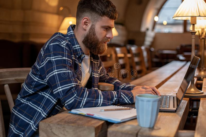Junger Fachmann, der das Internet auf seinem Laptop in einem Café surft lizenzfreies stockfoto