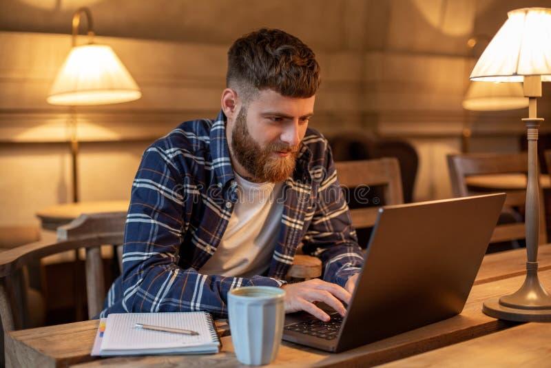 Junger Fachmann, der das Internet auf seinem Laptop in einem Café surft stockbild