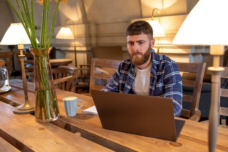 Junger Fachmann, der das Internet auf seinem Laptop in einem Café surft lizenzfreie stockfotografie