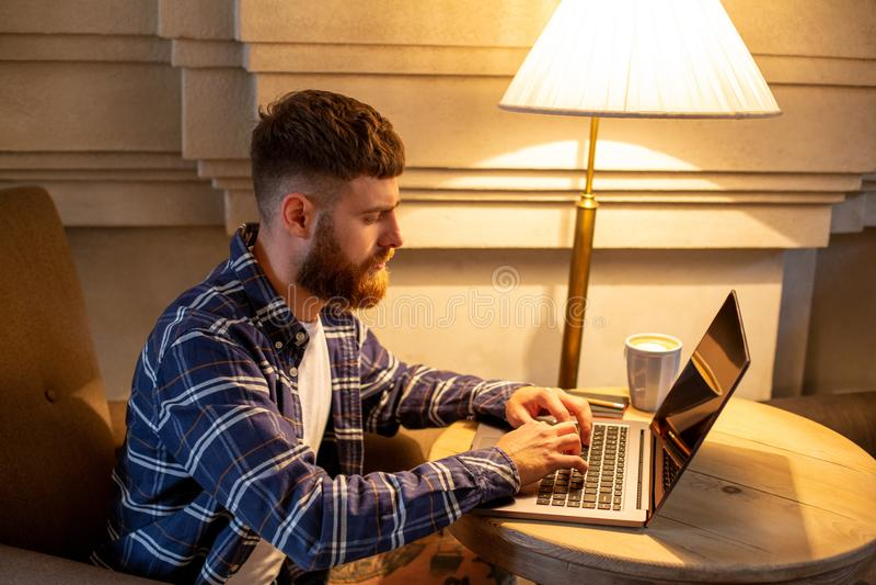 Junger Fachmann, der das Internet auf seinem Laptop in einem Café surft stockfoto