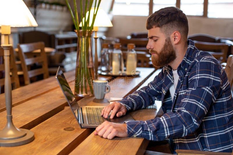 Junger Fachmann, der das Internet auf seinem Laptop in einem Café surft lizenzfreies stockbild