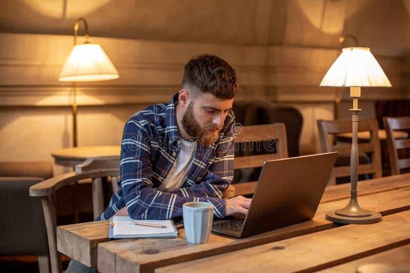 Junger Fachmann, der das Internet auf seinem Laptop in einem Café surft stockbilder