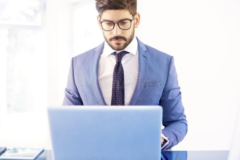 Junger Finanzberatergeschäftsmann, der Notizbuchweilearbeit verwendet stockbild