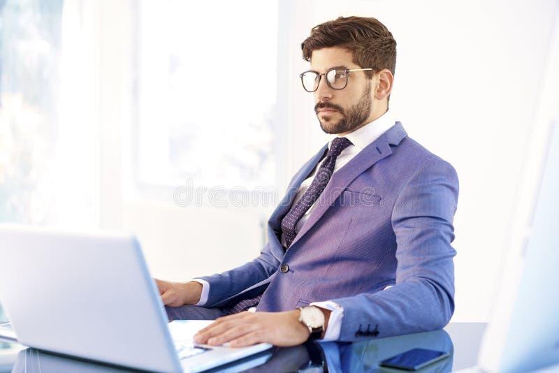 Junger Finanzberatergeschäftsmann, der Notizbuchweilearbeit verwendet lizenzfreie stockfotos