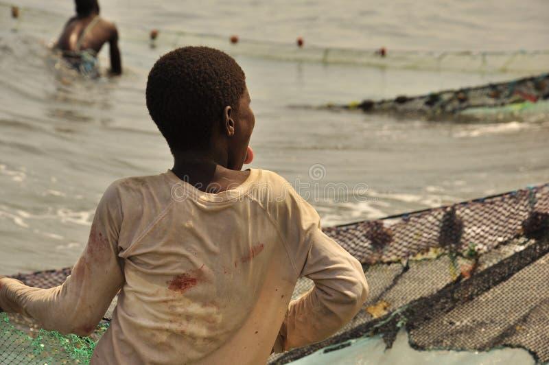Junger Fischer, der das Netz zieht stockbilder