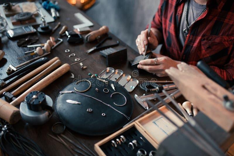 Junger fleißiger Handwerker, der das Einzelteil für Verkauf vorbereitet stockfoto