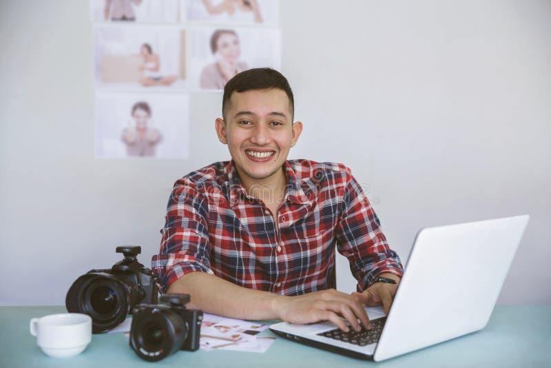 Junger Fotograf, der auf seinem Büro beim Arbeiten an Laptop sitzt lizenzfreie stockfotos