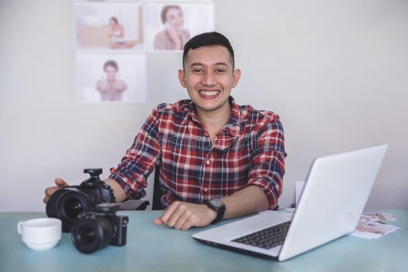 Junger Fotograf, der auf seinem Büro mit seinem Druckfoto bezüglich sitzt lizenzfreies stockfoto